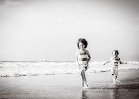 siblings running on the beach