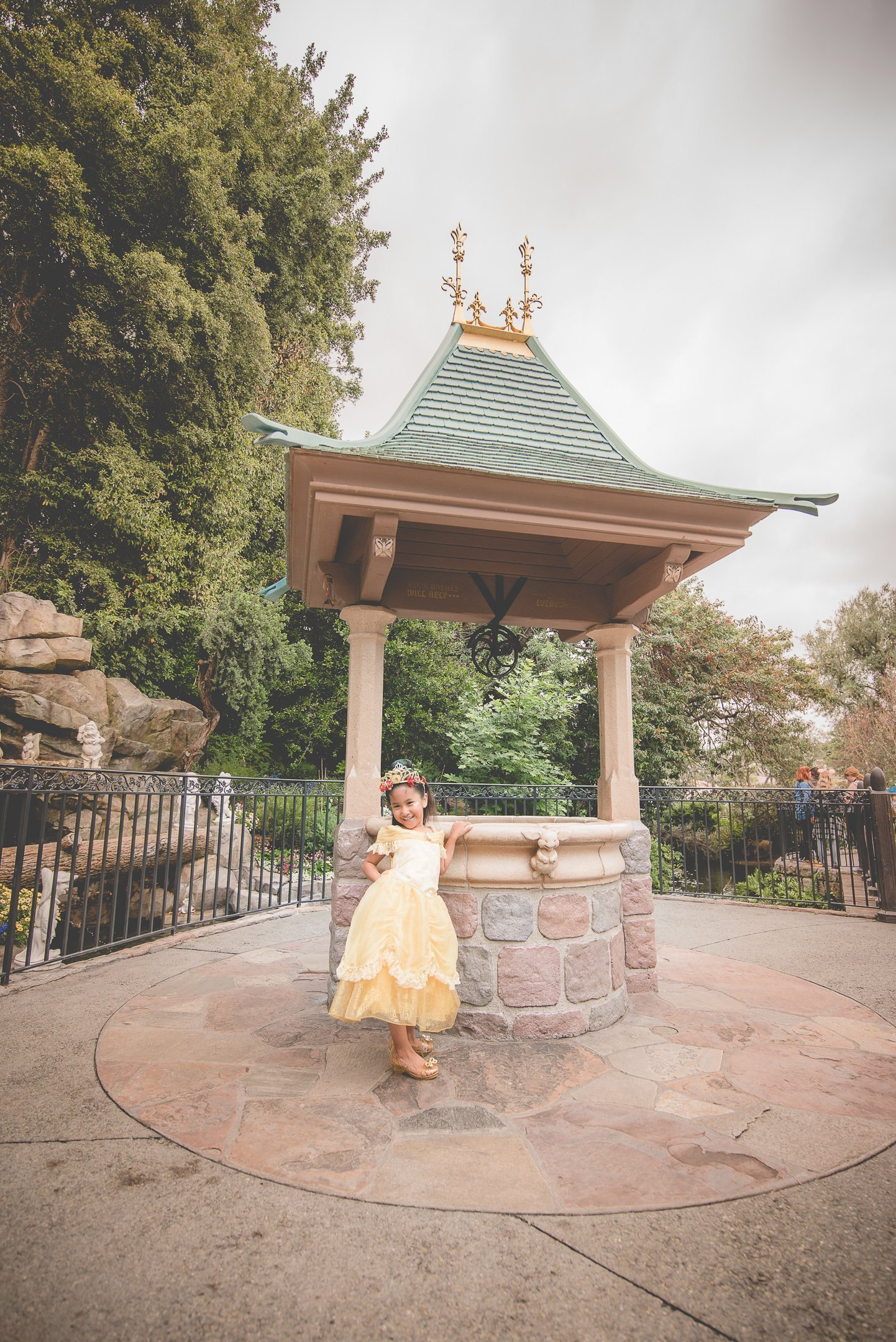Girl with princess dress standing in front of Snow White;s well