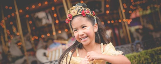 Girl with princess dress in front of King Arthur's Carousel