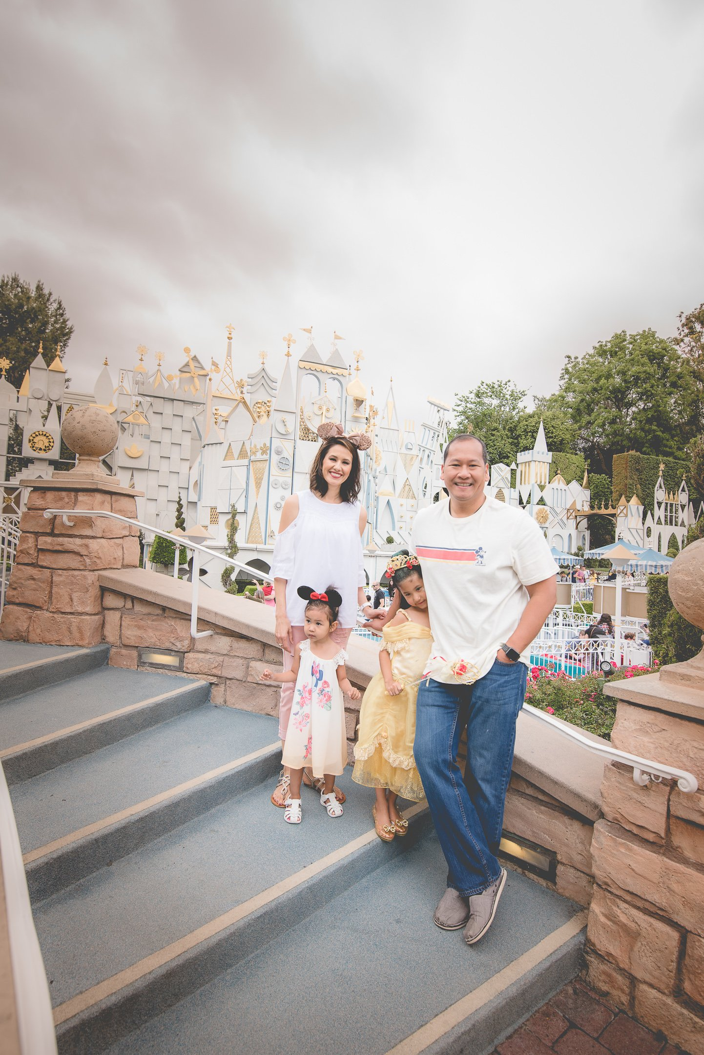Family photo by the It's a small world ride in Disneyland, CA