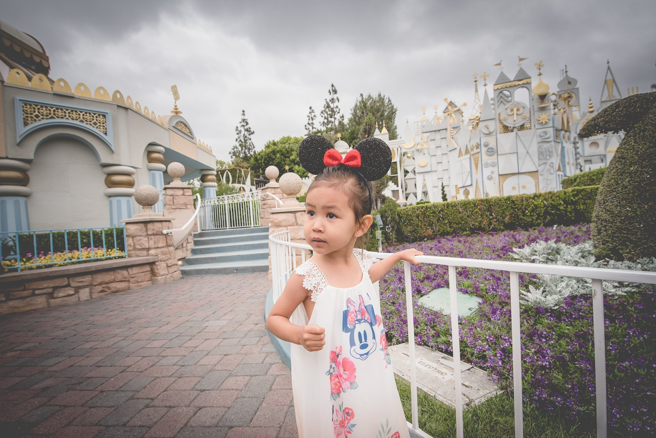 Little girl with Mickey ears by the It's a small world ride in Disneyland, CA