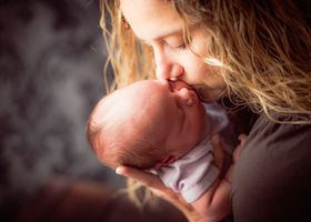 Photo of mother kissing newborn