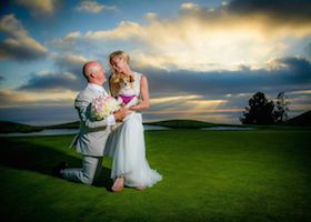 newlyweds posing with the sunset behind them