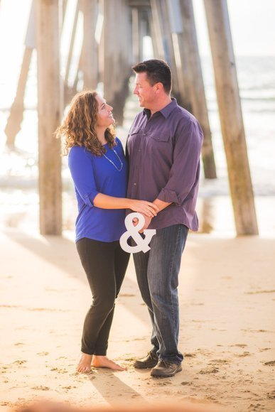 couple on the beach holding white ampersand sign