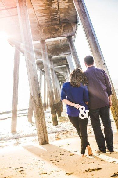 couple on the beach walking under pier