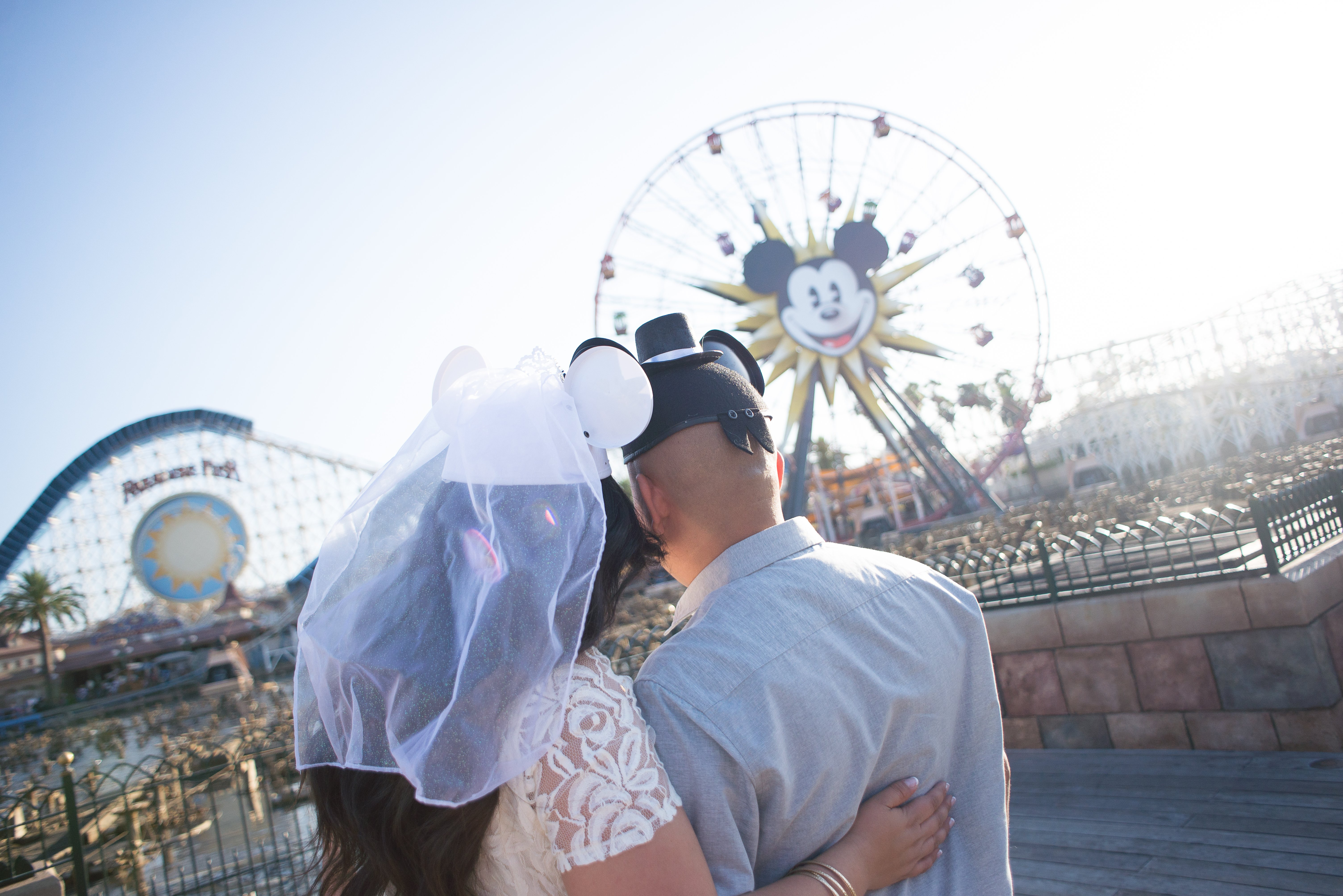 Couple standing in front of the mickey wheel, Example of hand correction service