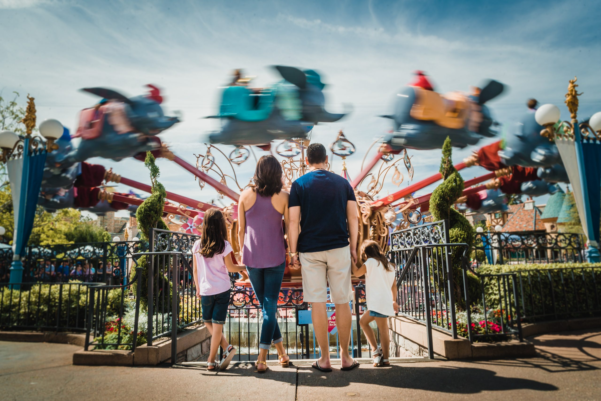 Family posing in front of the Dumbo ride in Disneyland