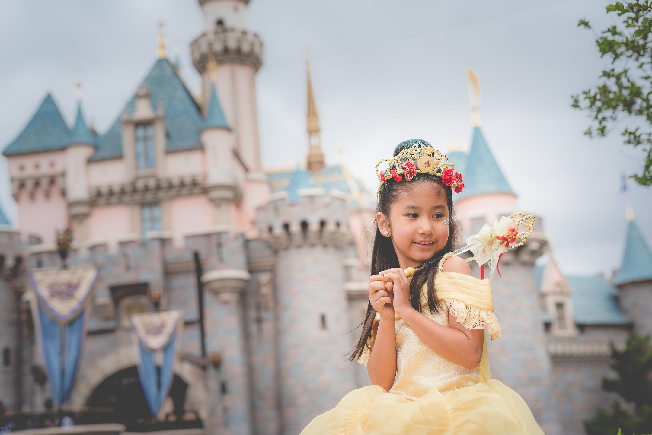 Girl with princess dress sitting in front of Disney's Sleeping Beauty Castle