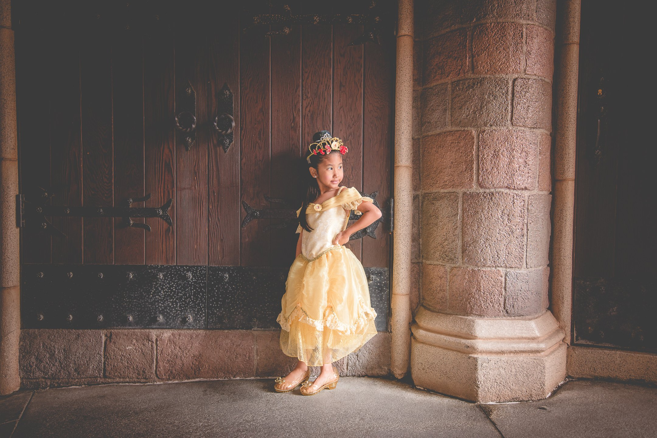 Girl with princess dress in a Disney hallway