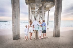 Family standing on the beach under pier
